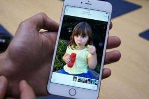 Hand holding iphone with the picture of kid